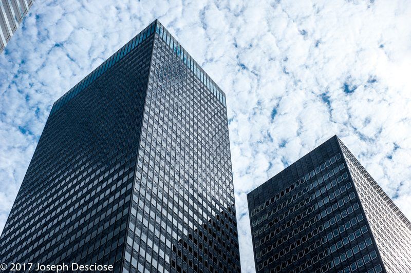 View looking up of cube shaped steel and glass buildings .