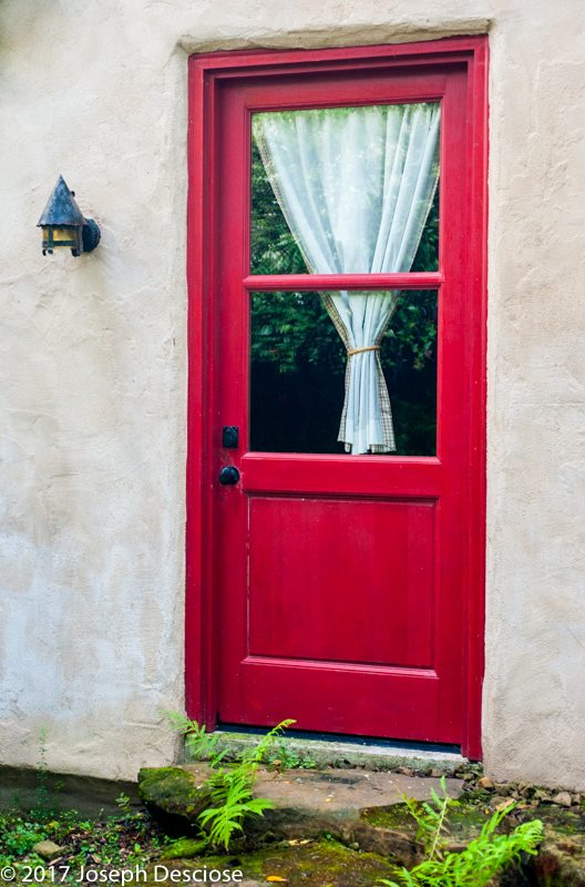 Red door with a curtain in the window on a house.