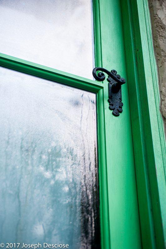 Door handle on a green door with glass panes.