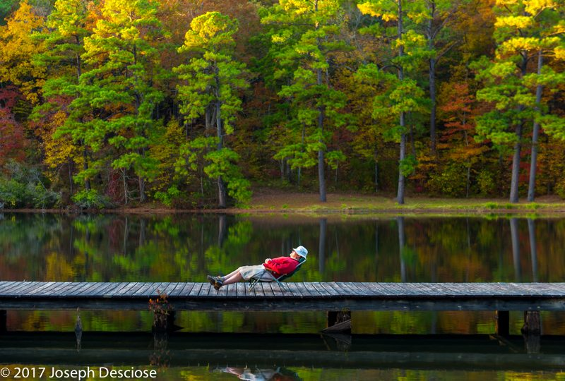 Man napping on a dock by a lake