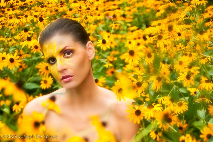 Portrait of a woman in a garden amongst Black Eyed Susans flowers.