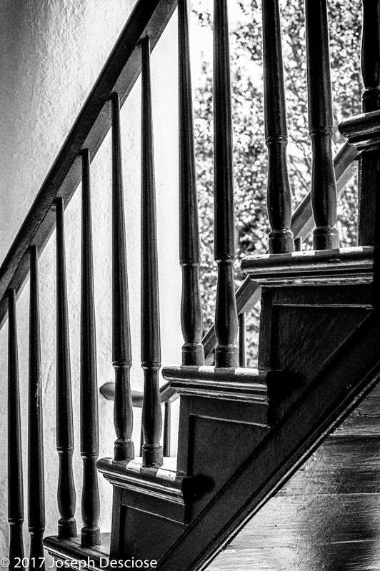 An architectural study of a wooden stairway in black & white.
