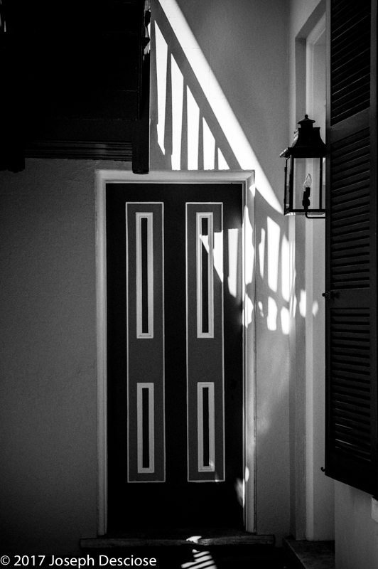 An architectural study of a wooden door in a hallway in black & white.