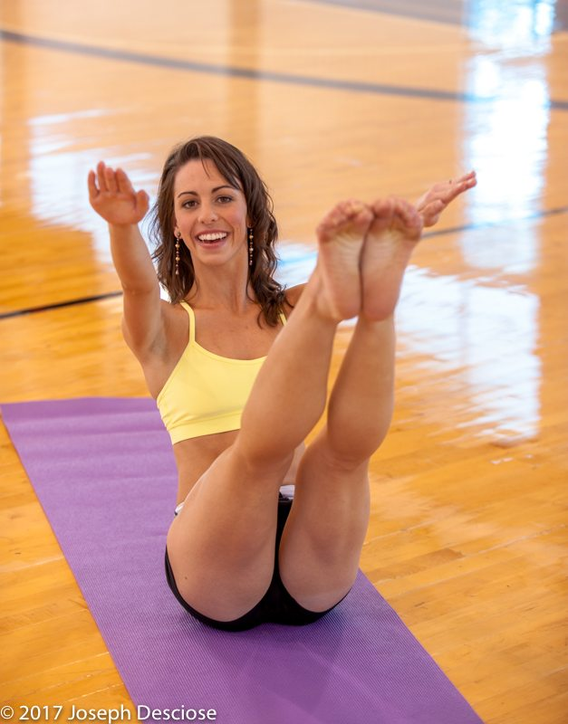 A 22 year old brunette woman doing a yoga pose indoors.