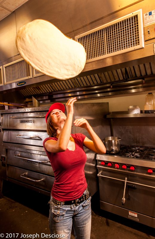 An 18 year old girl tosses pizza dough in a restaurant.