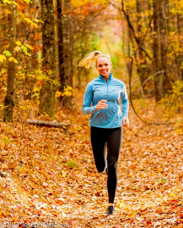 A 39 year old blond woman dressed in fitness clothing running in a forest in autumn.