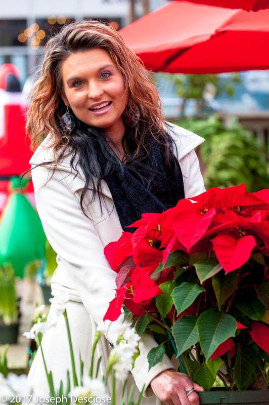 Young woman holding a poinsettia plant