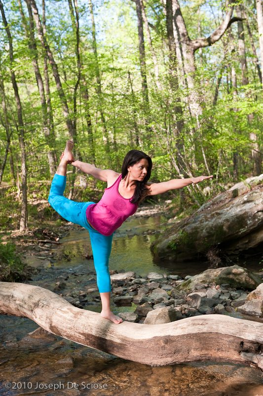 Young brunette woman doing yoga poses in a forest setting in the springtime.