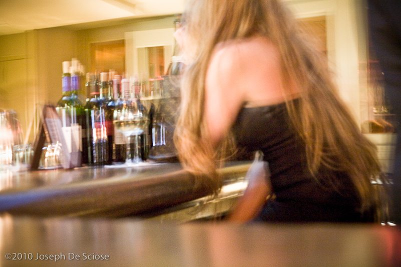 Blurry shot of a woman talking on a cell phone while sitting at a bar in New Orleans
